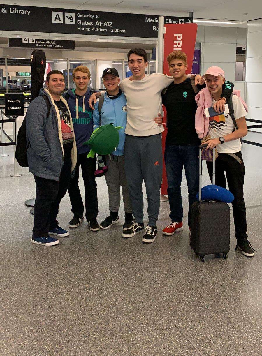 Gustavo (third from right) takes final picture with friends before getting on flight to California.