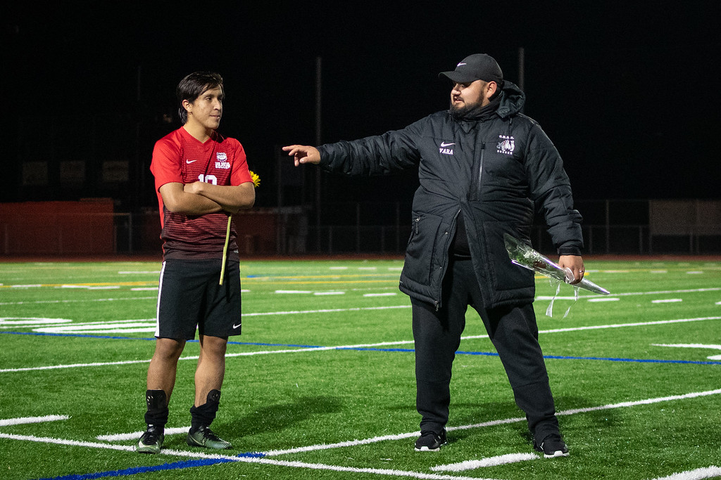 Chris Barrios, left, receives his senior night rose after his last MCAL game from coach Johnny Vara, right